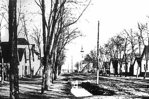 A Fõ utca a századelõn, háttérben a régi iskola másik szárnya, melyben két tanterem, a tanári és az igazgatói szobák voltak.